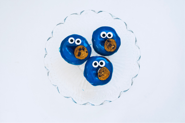 adding mini chocolate chip cookies to cookie monster donuts
