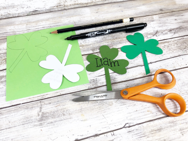 cutting out shamrock shapes and writing names on them