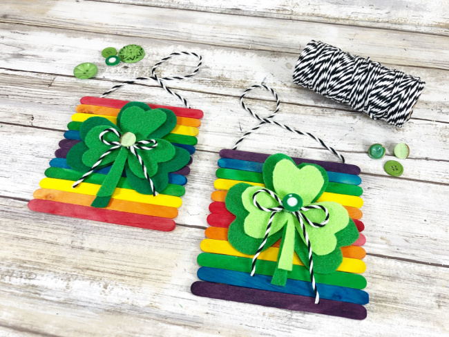 attaching baker's twine to wooden stick rainbow and shamrock signs as hangers