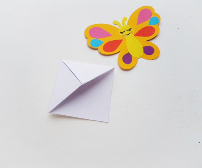 Make an origami paper corner bookmark to form the base for the butterfly